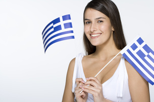 Young woman holding Greek flagsの写真素材 [FYI02131360]