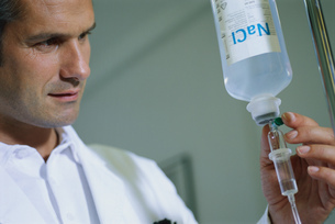 Low angle view of a male doctor adjusting an IV dripの写真素材 [FYI02131404]