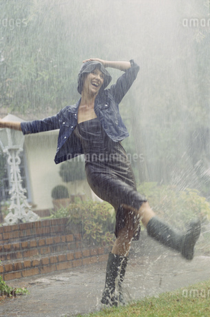 Woman in rubber boots playing outside in rainの写真素材 [FYI02131434]