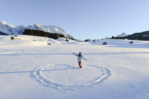 Young woman making heart shape in snowの写真素材 [FYI02131467]