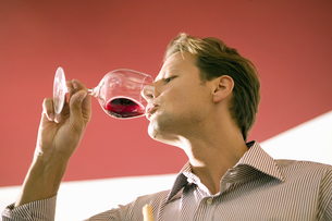 Low angle view of man drinking glass of red wineの写真素材 [FYI02131535]