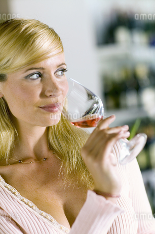Woman smelling rose wine in glass at wine tastingの写真素材 [FYI02131551]