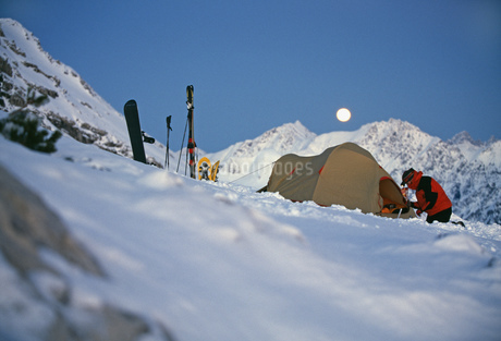 View of a young man setting up camp in the snow, Bivouac, Nebelhorn area, Bavaria, Germanyの写真素材 [FYI02131567]