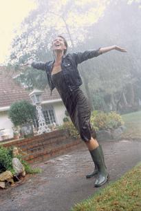 Woman in rubber boots enjoying rainの写真素材 [FYI02131594]