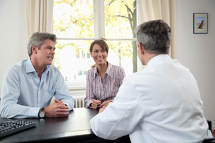 Doctor talking to couple in officeの写真素材 [FYI02131604]