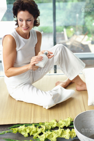 Portrait of a young woman using hand lotion whilst sitting on a straw matの写真素材 [FYI02131615]