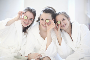 Portrait of teenage girls holding up cucumber slicesの写真素材 [FYI02131623]