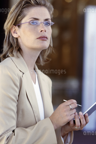 Woman using a PDA, looking upの写真素材 [FYI02131838]