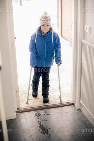 Portrait of disabled girl with crutches entering houseの写真素材 [FYI02131943]