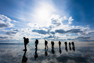 Silhouetted people skiing on frozen lake against cloudy skyの写真素材 [FYI02132018]