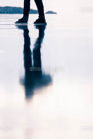 Low section of person ice-skating on frozen lakeの写真素材 [FYI02132046]