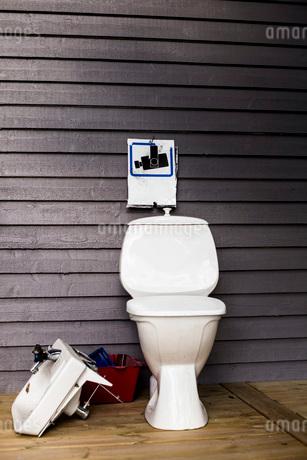 Broken sink and toilet against wooden wallの写真素材 [FYI02132083]