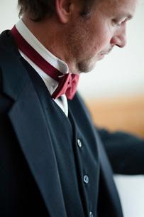 Mature man in tuxedo looking downの写真素材 [FYI02132179]