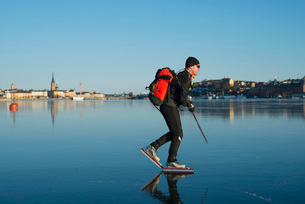 Side view of man with backpack skating on frozen lakeの写真素材 [FYI02132298]