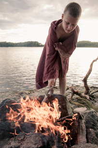 Boy wrapped in towel standing by bonfire at lakeの写真素材 [FYI02132486]