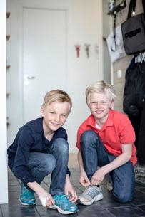 Portrait of smiling boys tying shoe laces on floorの写真素材 [FYI02132538]