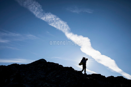 Silhouette of female hiker walking on rocks against skyの写真素材 [FYI02132541]