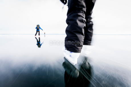 People skiing on frozen lake against clear skyの写真素材 [FYI02132551]