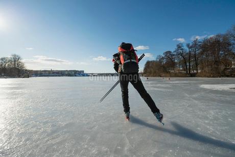 Rear view of man skating on frozen lakeの写真素材 [FYI02132611]