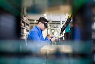 Side view of male technician wearing protective eyewear workの写真素材 [FYI02132619]