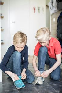 Young boys tying shoe laces on floorの写真素材 [FYI02132669]
