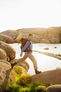 Side view of female backpacker hiking on rocksの写真素材 [FYI02132678]