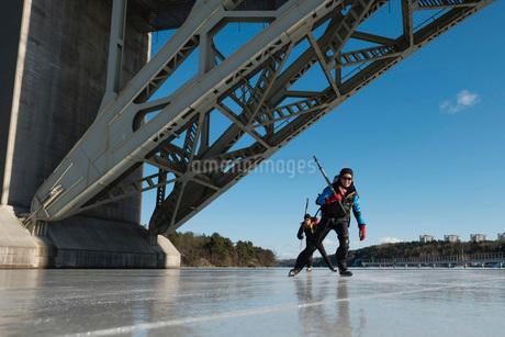 Man and woman skating under bridgeの写真素材 [FYI02132774]