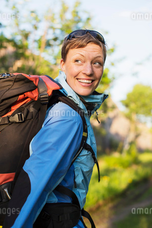 Female hiker with backpack looking over shoulder outdoorsの写真素材 [FYI02132865]