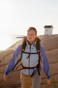 Female backpacker looking away while walking against rockの写真素材 [FYI02132904]