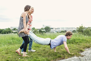 Happy young women holding male friends legs doing push-ups on fieldの写真素材 [FYI02132979]