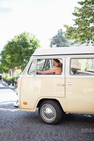 Man driving mini van on streetの写真素材 [FYI02133021]