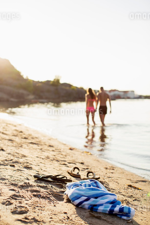 Towel and flip-flops on lakeshore with couple walking in lakeの写真素材 [FYI02133082]