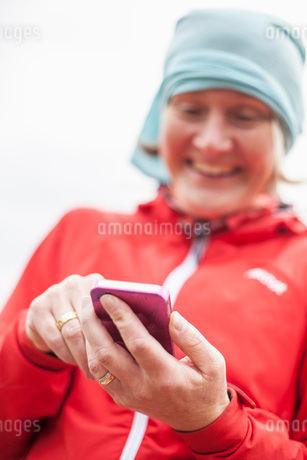 Happy mature woman in red jacket using mobile phone outdoorsの写真素材 [FYI02133138]