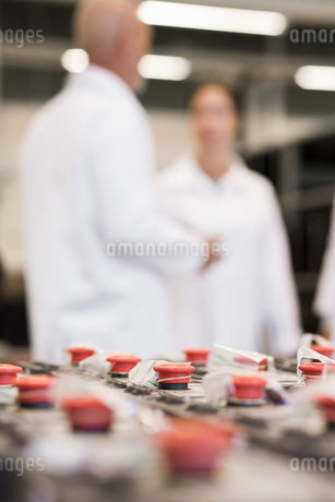Selective focus on machine parts with engineers in background at industryの写真素材 [FYI02133160]