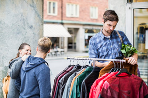 Young man selecting jackets with friends passing by clothing storeの写真素材 [FYI02133172]