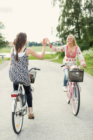 Happy female friends giving high five while cycling on country roadの写真素材 [FYI02133224]