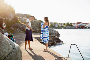 Full length of couple wrapping themselves in towel at lakeshoreの写真素材 [FYI02133244]