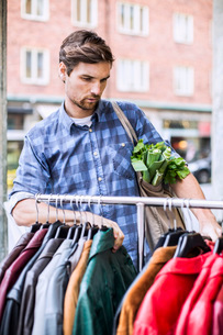 Young man with groceries selecting jackets in clothing storeの写真素材 [FYI02133286]