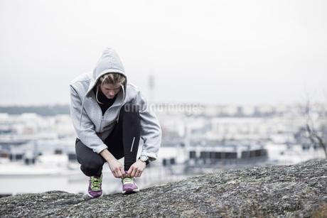 Full length of sporty woman tying shoe lace on rockの写真素材 [FYI02133401]