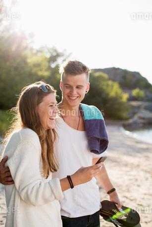 Happy couple spending leisure time on lakeshoreの写真素材 [FYI02133583]