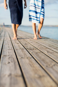 Low section of couple wrapped in towels walking on wooden pierの写真素材 [FYI02133593]