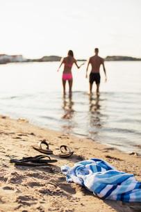 Towel and flip-flops on lakeshore with couple enjoying in lakeの写真素材 [FYI02133742]