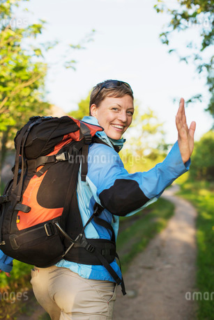 Portrait of happy female backpacker waving while hiking at forestの写真素材 [FYI02133760]