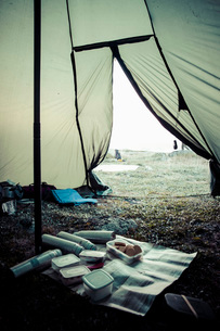 Food containers and thermoses in tent at campsiteの写真素材 [FYI02133791]