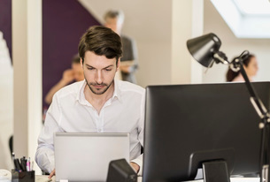 Businessman using laptop at desk in officeの写真素材 [FYI02133807]