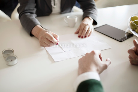 Cropped image of businesswoman drawing while explaining colleague at deskの写真素材 [FYI02133897]