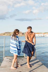 Playful woman pulling man's towel on pierの写真素材 [FYI02133922]