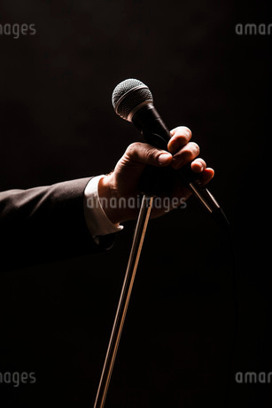 Hand holding microphone over black backgroundの写真素材 [FYI02133954]