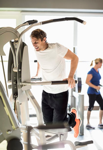 Man exercising on pull-up assist machine at gymの写真素材 [FYI02134058]