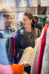 Happy friends shopping for sweaters in clothing storeの写真素材 [FYI02134105]